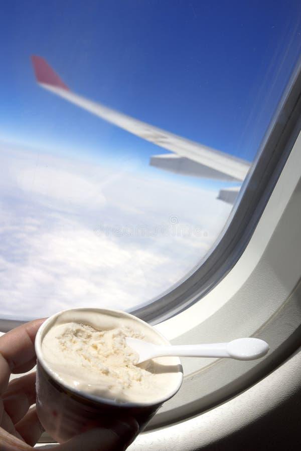 Appréciez la crème glacée dans l'avion par la fenêtre avec le ciel bleu photo libre de droits