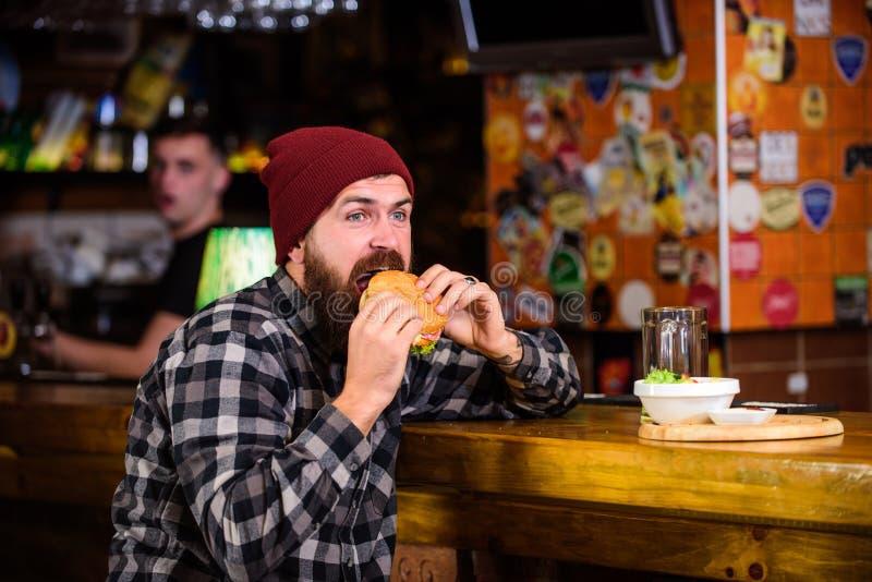 Appréciez le goût de l'hamburger frais L'homme affamé de hippie mangent l'hamburger L'homme avec la barbe mangent le menu d'hambu photos stock