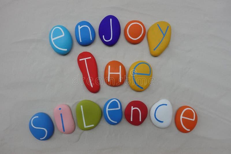 Appréciez le texte de silence avec les pierres colorées au-dessus du sable blanc photo libre de droits