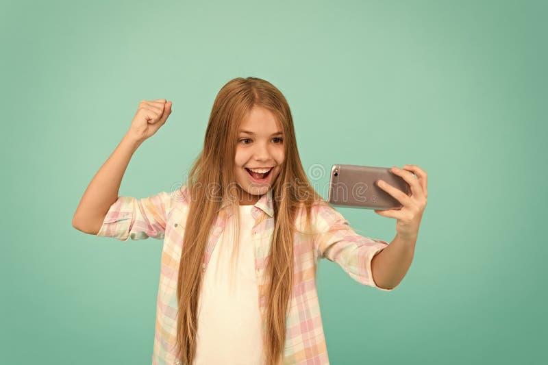 Appr?cier la vid?o en direct Petite fille ? l'aide du t?l?phone portable Enfant adorable apprenant la nouvelle technologie T?l?ph photographie stock libre de droits