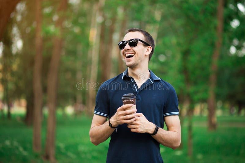 Appr?cier le caf? frais Jeune homme beau dans la tenue de d?tente tenant la tasse jetable et souriant tout en marchant par la vil images stock