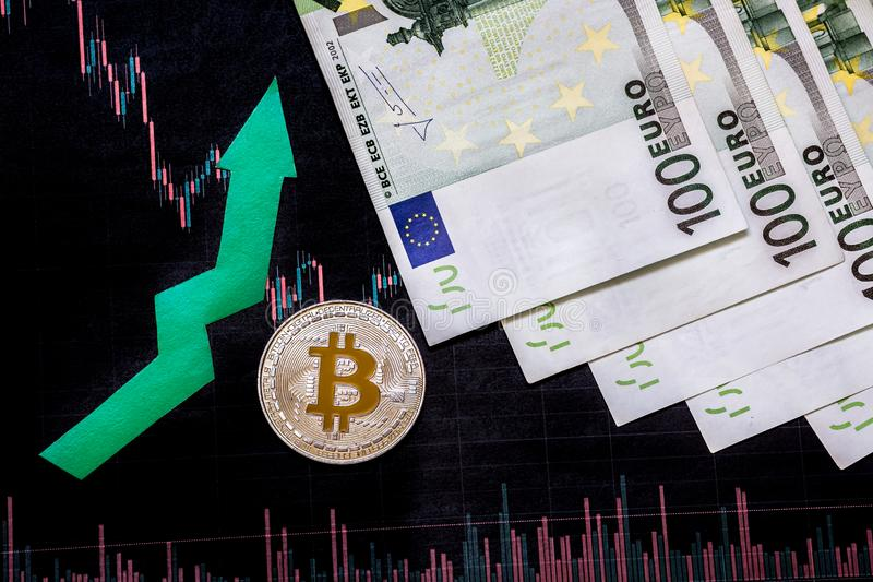 Appreciation of virtual money bitcoin. Green arrow and silver Bitcoin on hundred euro bills and paper forex chart index rating on stock photography