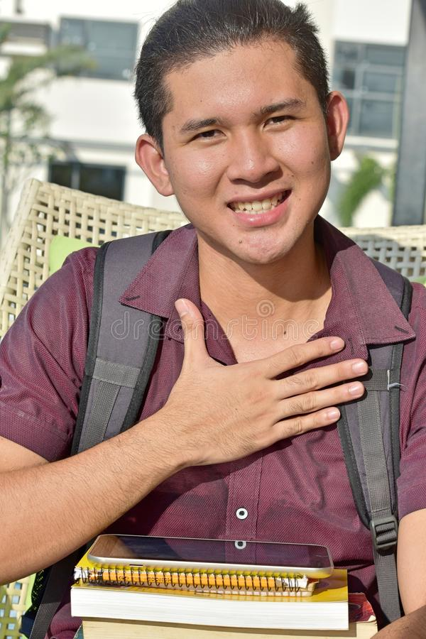 Appreciative Male Student With Notebooks. An attractive and asian person royalty free stock photo