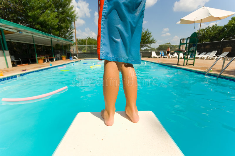 Apprehension. Young boy standing on the end of a diving board at a swimming pool royalty free stock photos
