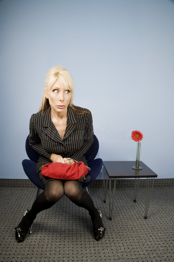 Apprehensive woman sitting waiting in an office royalty free stock photography