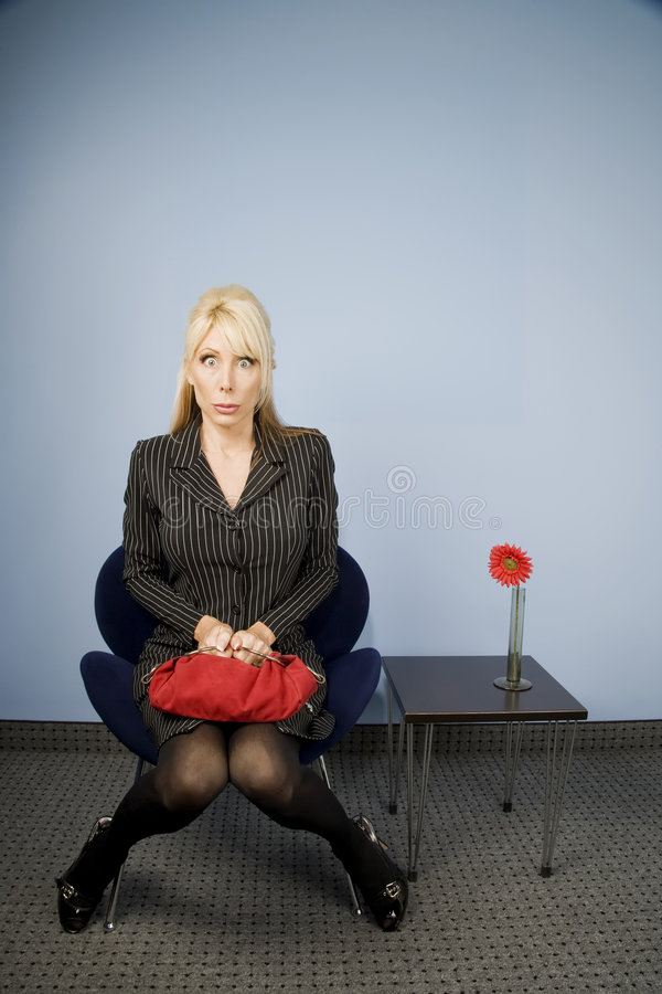 Apprehensive woman sitting waiting in an office ch stock images