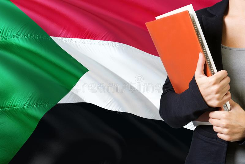 Apprendimento del concetto sudanese di lingua Condizione della giovane donna con la bandiera del Sudan nei precedenti Insegnante  fotografia stock libera da diritti