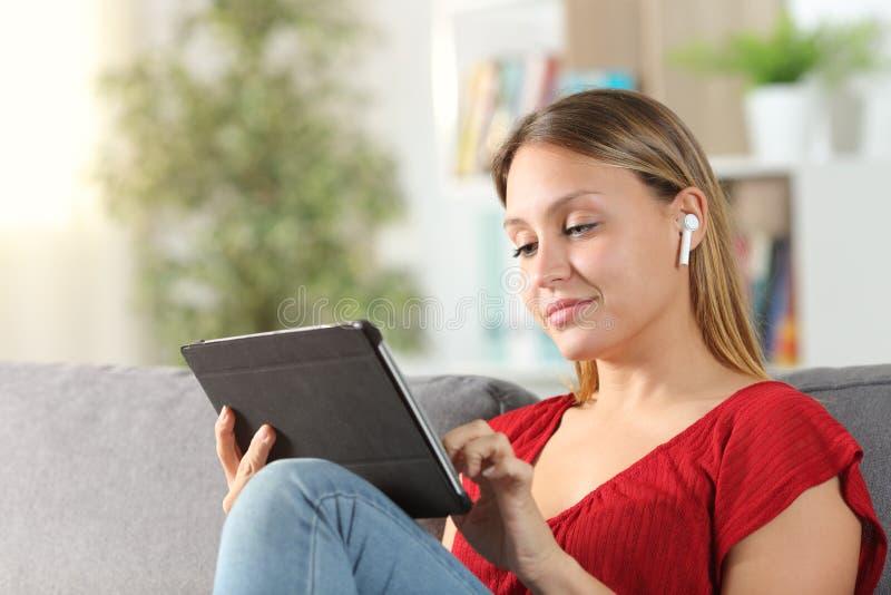 Apprendimento elettronico femminile con tablet e cuffie da casa immagini stock