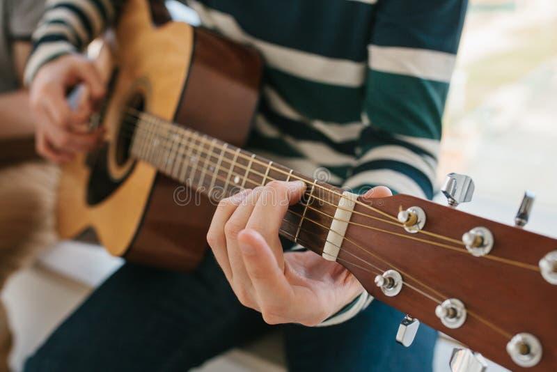 Apprendimento giocare la chitarra Istruzione di musica e lezioni extracurriculari Hobby ed entusiasmo per il gioco della chitarra fotografia stock libera da diritti