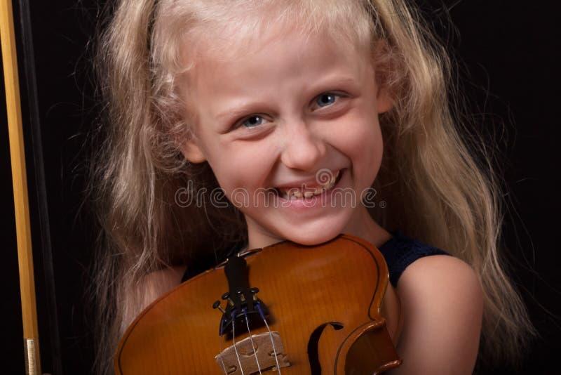Apprendimento giocare Violino sorridente della tenuta della bambina in mani su fondo scuro immagini stock libere da diritti