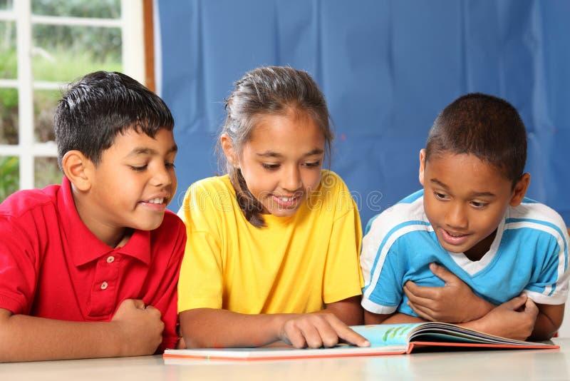 Apprendimento insieme dei tre bambini giovani felici del banco immagini stock libere da diritti
