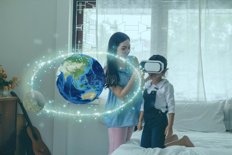 Apprendimento intelligente con il concetto di educazione alla realtà virtuale mista potenziato, la madre cerca di insegnare alla  fotografie stock