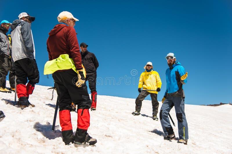 Apprendimento slittare correttamente su un pendio o su un ghiacciaio con un'ascia di ghiaccio immagini stock