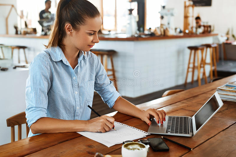 Apprendimento, studiando Donna che per mezzo del computer portatile al caffè, lavorante fotografie stock libere da diritti