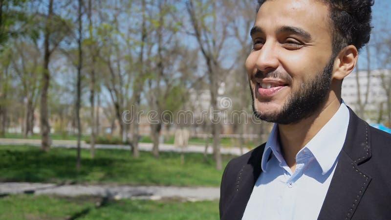 Apprendista che cammina nel parco dopo il lavoro, sorridente con le fossette sul fronte fotografia stock
