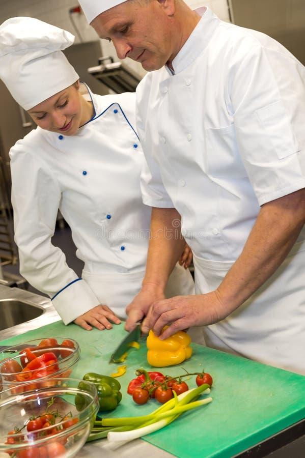 Apprendista che impara le verdure di taglio dal cuoco unico immagine stock