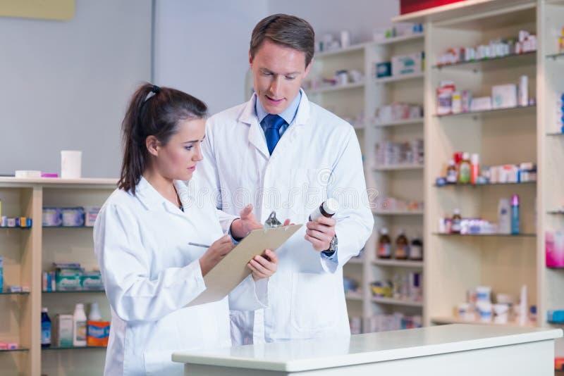 Apprendista che tiene una prescrizione mentre parlando con farmacista fotografia stock