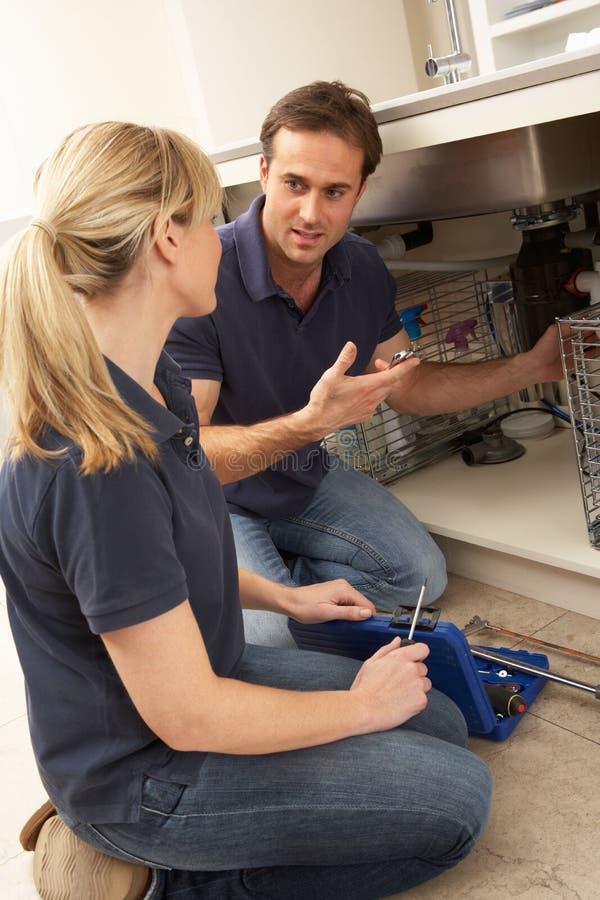 Apprendista d'istruzione dell'idraulico per riparare il dispersore di cucina fotografia stock