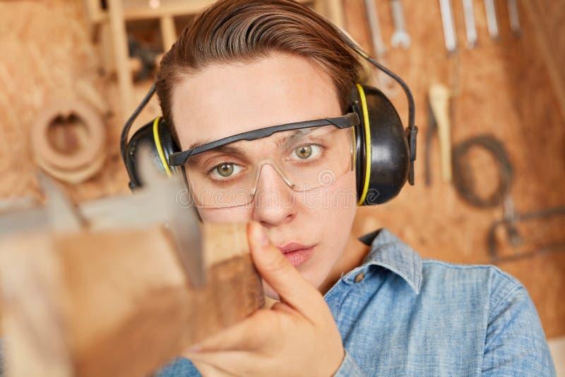Apprendista del carpentiere mentre misurando legno fotografia stock libera da diritti