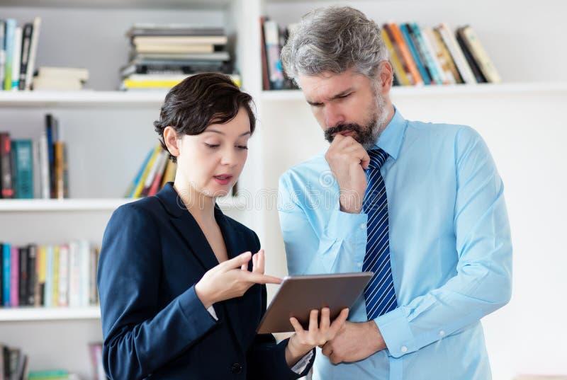 Apprendista femminile ed uomo d'affari tedesco di pensiero con capelli grigi che esaminano il computer della compressa fotografia stock libera da diritti