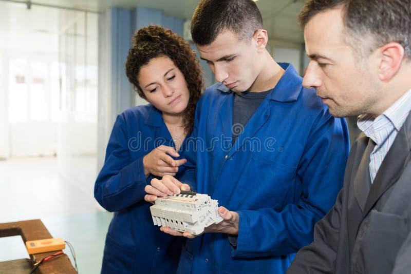 Apprendisti che esaminano la scatola di giunzione elettrica fotografia stock libera da diritti