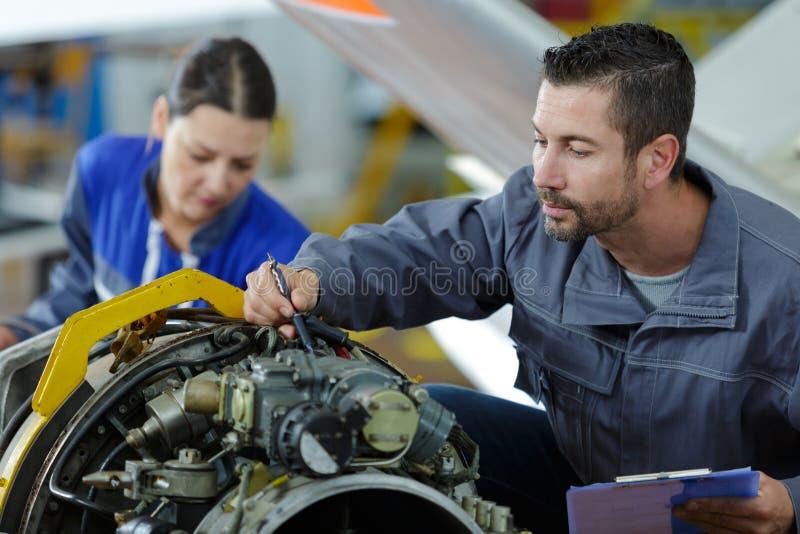 Apprenti étudiant des moteurs de voiture avec le mécanicien images libres de droits