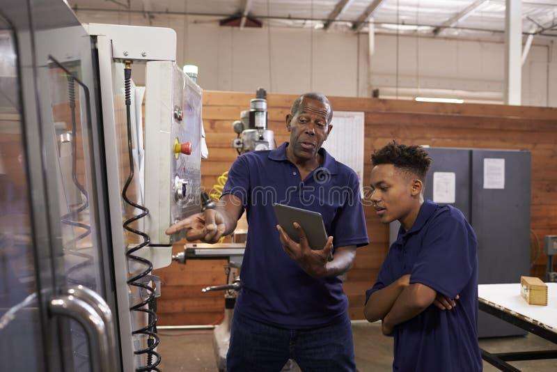 Apprenti de Training Young Male d'ingénieur sur la machine de commande numérique par ordinateur photos stock