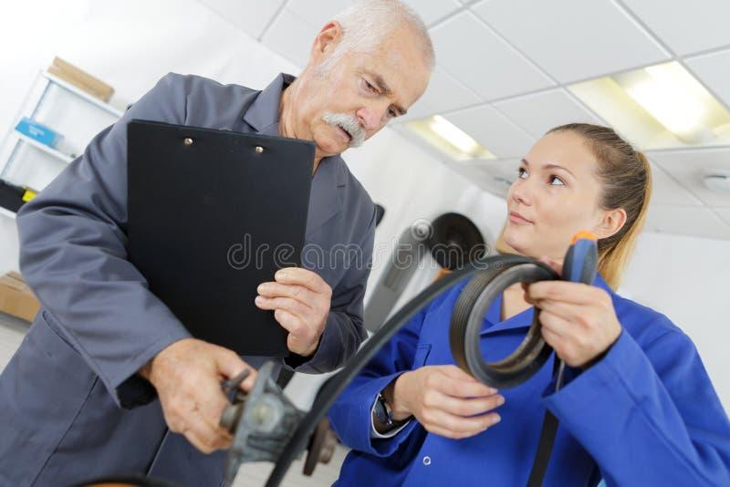 Apprenti montrant le caoutchouc de longueur au tuteur image libre de droits