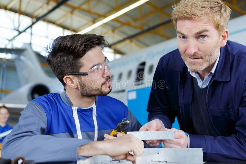 Apprentice aerospace engineer talking to superior royalty free stock images