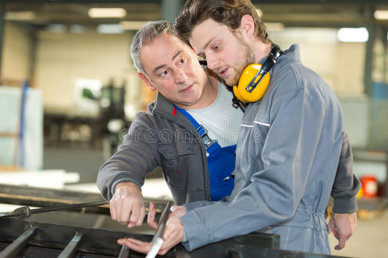 Apprentice being guided by teacher royalty free stock images