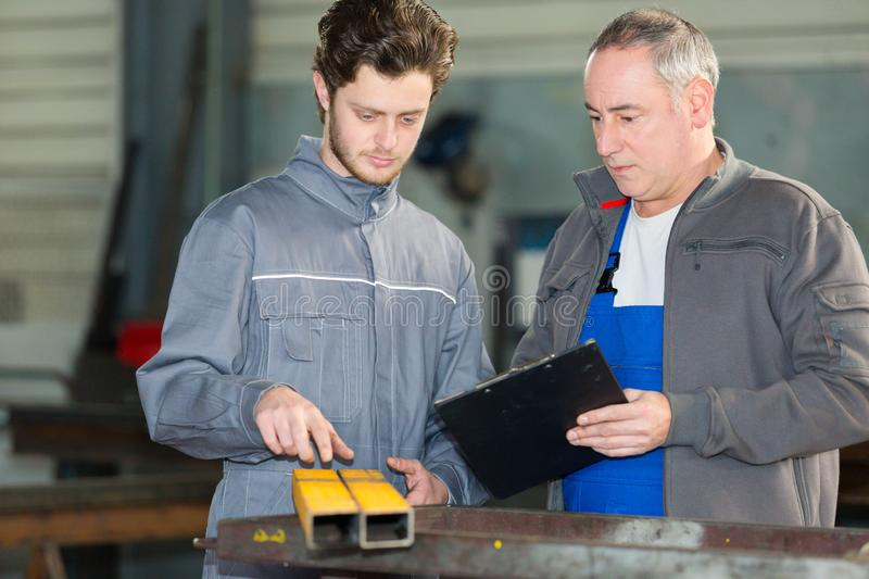 Apprentice being shown how to cut sheet metal royalty free stock photography