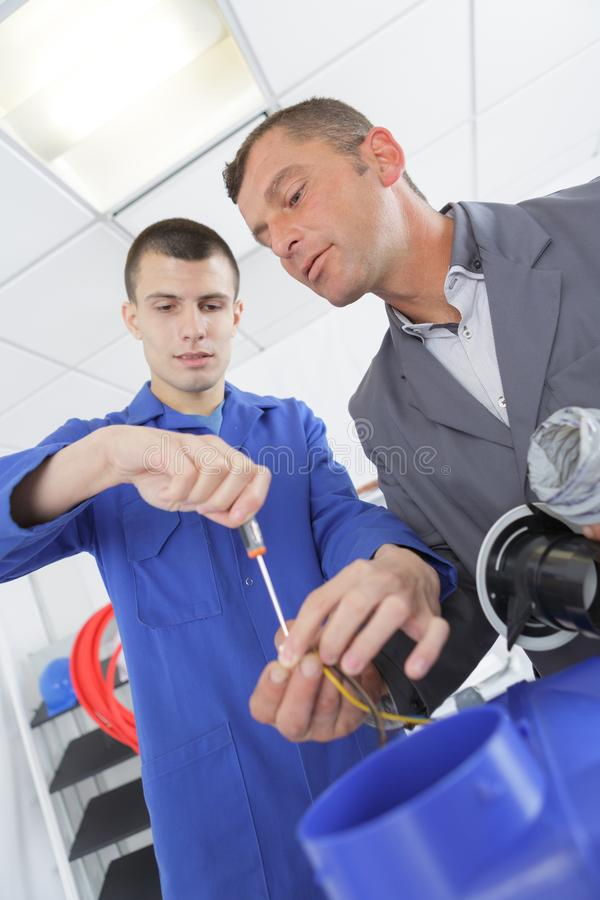 Apprentice being supervised by teacher royalty free stock photography