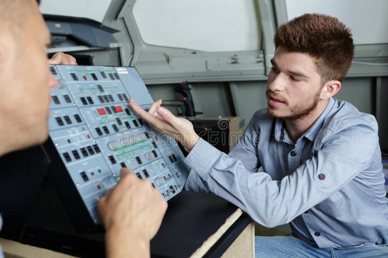 Apprentice being taught controls machine stock photo
