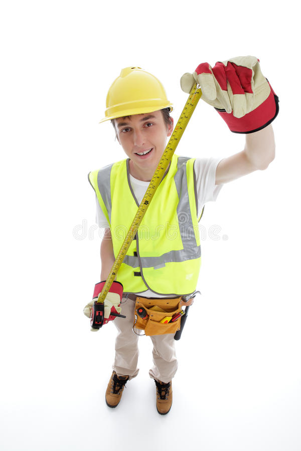 Apprentice builder or carpenter. Holding an outstretched measureing tape. White background stock image