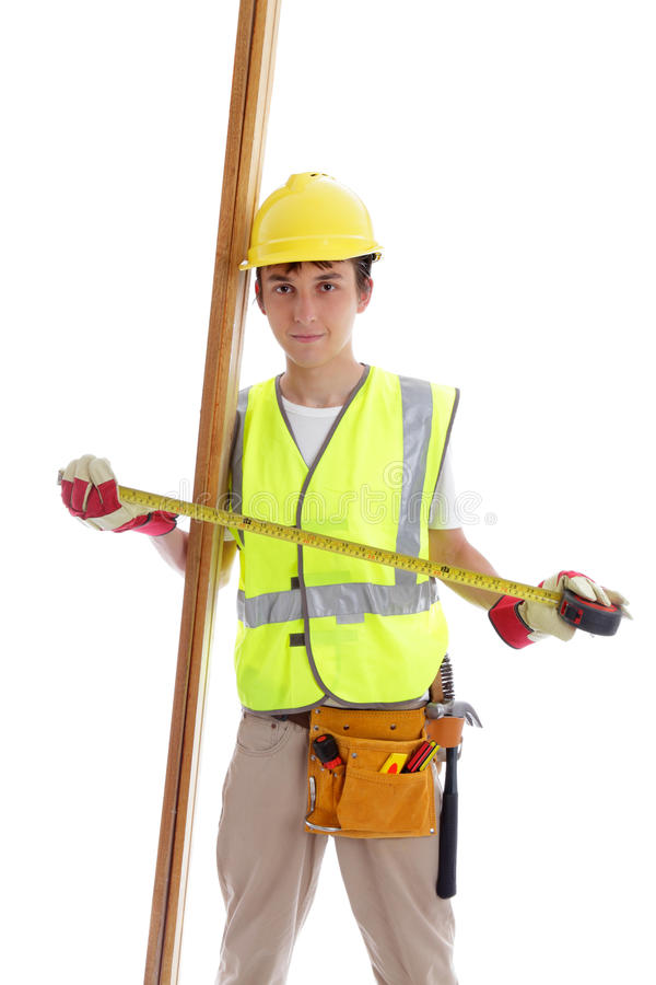 Apprentice builder carpenter. Apprentice builder or carpenter holding a tape measure and pieces of timber wood. White background stock image