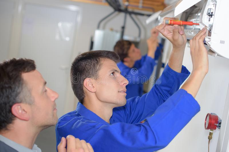 Apprentice electrician being watched at work royalty free stock image