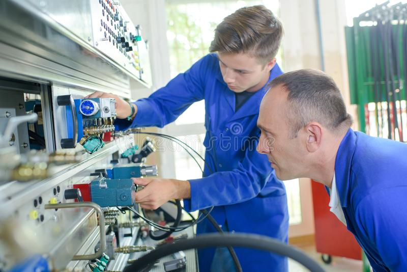 Apprentice electrician under supervision royalty free stock image