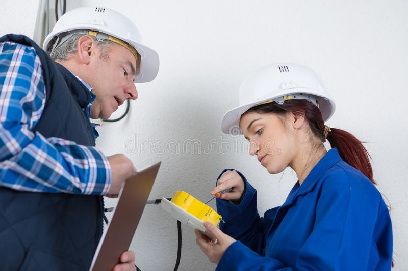 Apprentice electrician unscrewing junction box stock photography