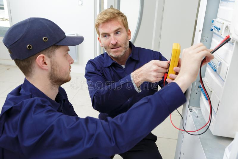 Apprentice electrician using multimeter on fusebox royalty free stock images