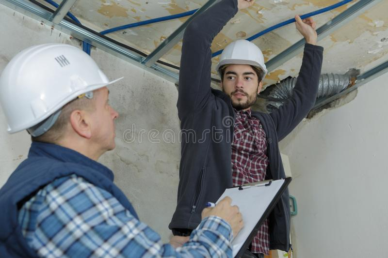 Apprentice electrician wiring large room stock photography