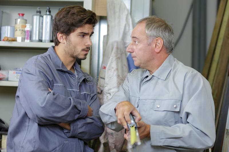 Apprentice engineer working on factory floor. Worker royalty free stock photography