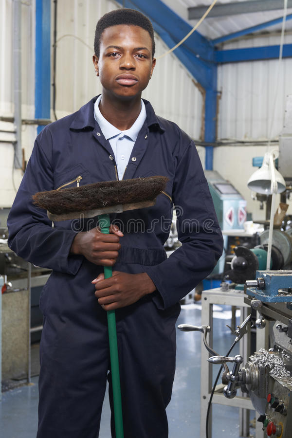 Apprentice In Engineering Factory Sweeping Floor. Portrait Of Apprentice In Engineering Factory Sweeping Floor royalty free stock photography