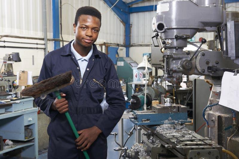 Apprentice In Engineering Factory Sweeping Floor. Portrait Of Apprentice In Engineering Factory Sweeping Floor stock photo