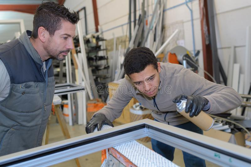 Apprentice glazier and mentor in factory workshop stock image