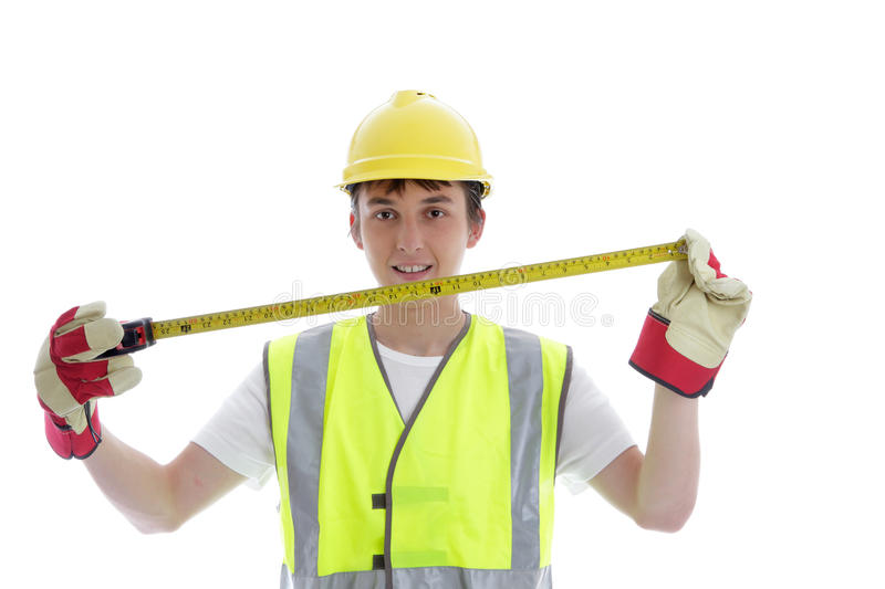 Apprentice holding builders tape measure. Young apprentice holding a builders tape measure and smiling royalty free stock image