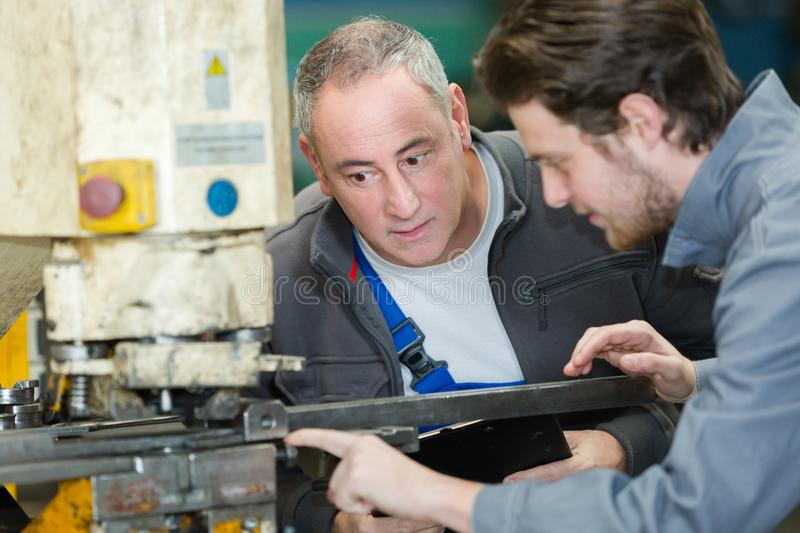 Apprentice learning to operate machine. Apprentice learning to operate a machine royalty free stock photography