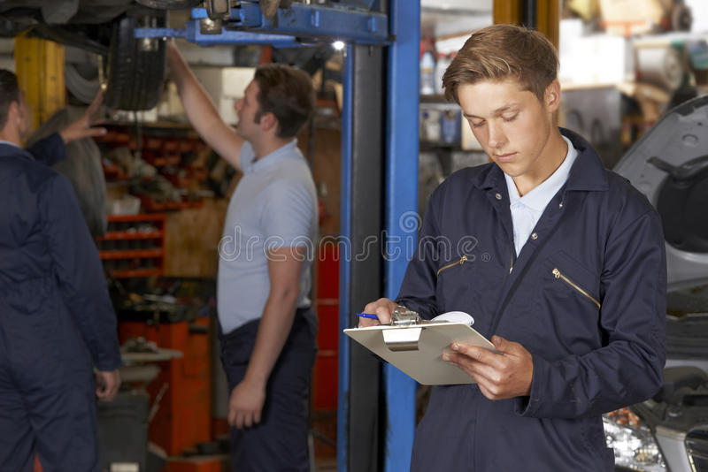 Apprentice Mechanic Working In Auto Repair Shop. Male Apprentice Mechanic Working In Auto Repair Shop royalty free stock images