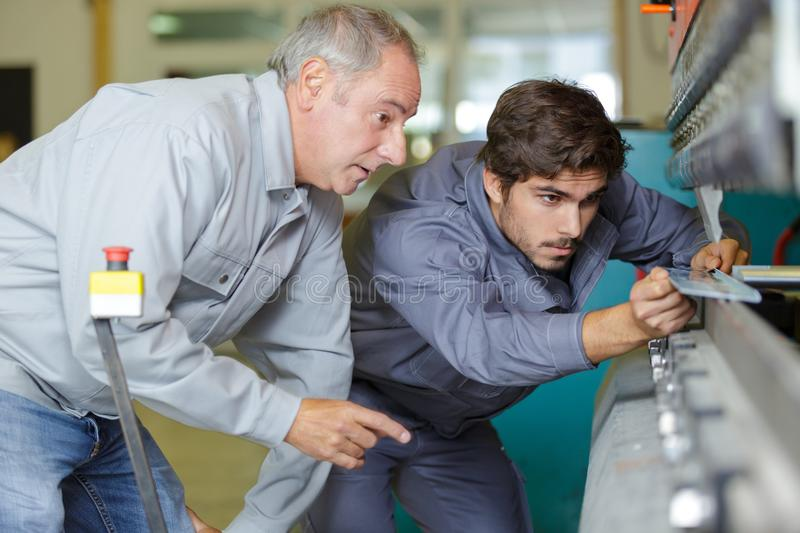 Apprentice mechanical technician measuring cutting tool at tool workshop. Apprentice royalty free stock photography