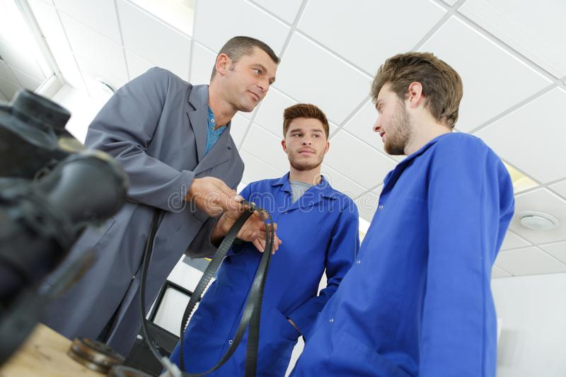 Apprentice mechanics in auto shop working on car engine royalty free stock photos