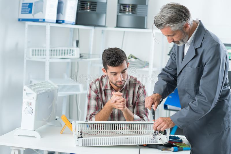 Apprentice repairing appliance with mentor. Apprentice repairing appliance with his mentor stock photography